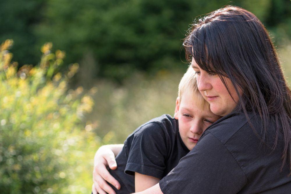 Mama tröstet Kind nach Tod des Hundes