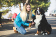 Beautiful blond young woman enjoying with her adorable Bernese Mountain dog.