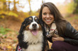 Cute girl with her Dog in Autumn park. Bernese Mountain Dog